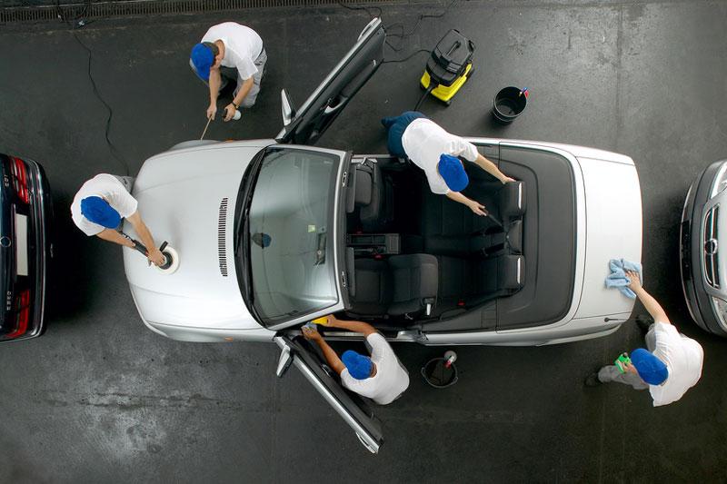 Draufsicht eines Putz-Teams bei der Reinigung eines PKW