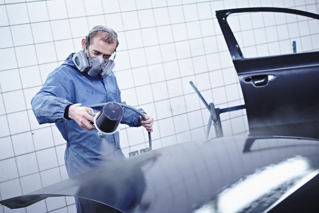 Bild zeigt Mitarbeiter bei der Lackierung einer Motorhaube vom PKW